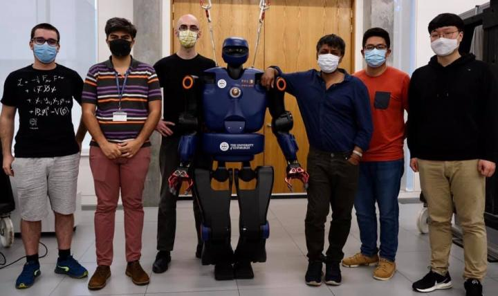 6-foot humaoid robot Talos stands with six members of the robotics research lab, all in masks